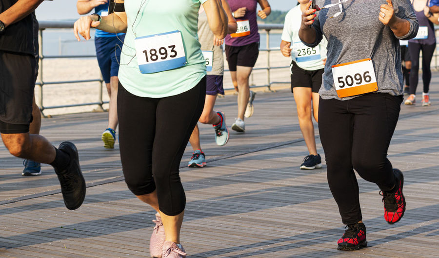Many runners on a boardwalk are racing a 10k on a summer night at sunken meadow state park.