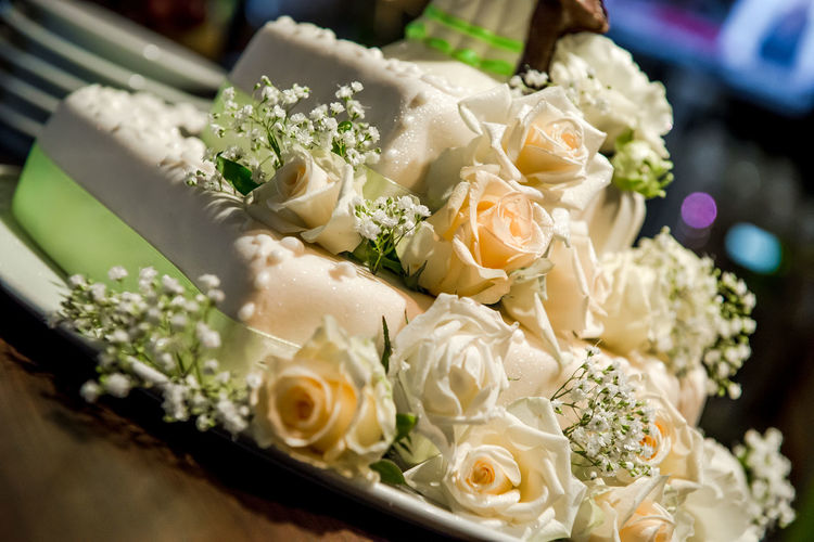 Close-Up Of Wedding Cake Decorated With Roses On Table
