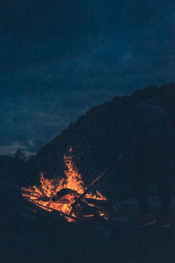 Man with campfire against sky at night