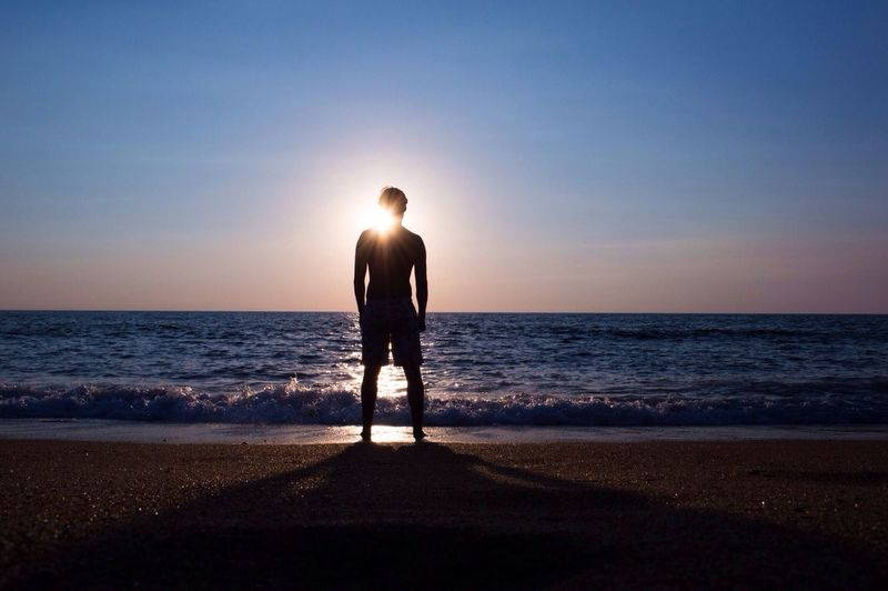 Silhouette Person Standing At Seashore Against Sky During Sunset