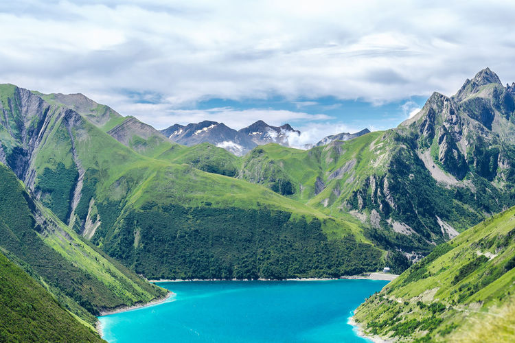 Scenic View Of Lac De Grand Maison Amidst Rocky Mountains Against Cloudy Sky