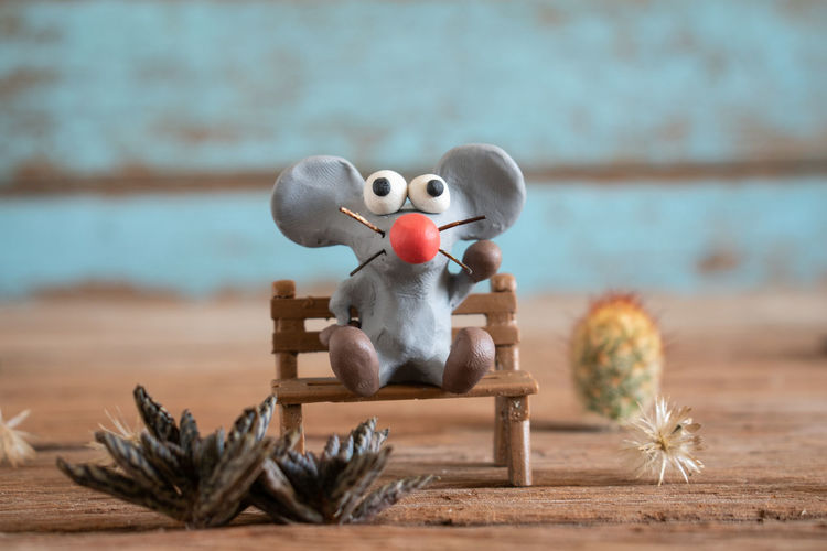 Rat from plasticine,cartoon style.the background is blue wood panels.