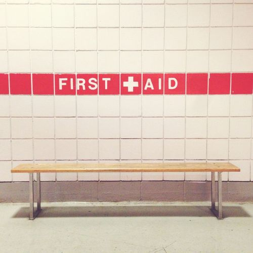 Empty bench against first aid text on wall