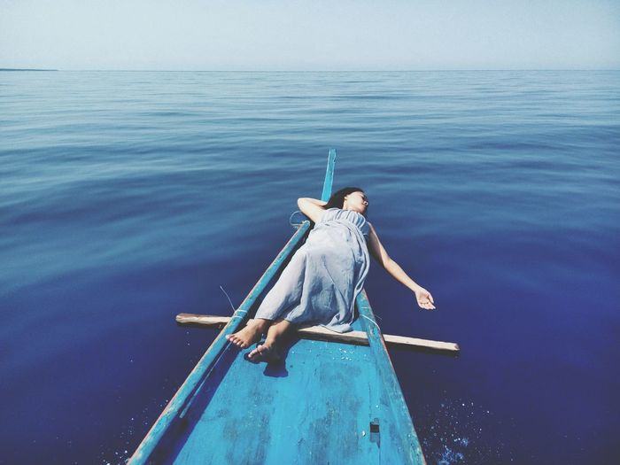 High Angle View Of Woman Lying On Boat In Sea Against Sky