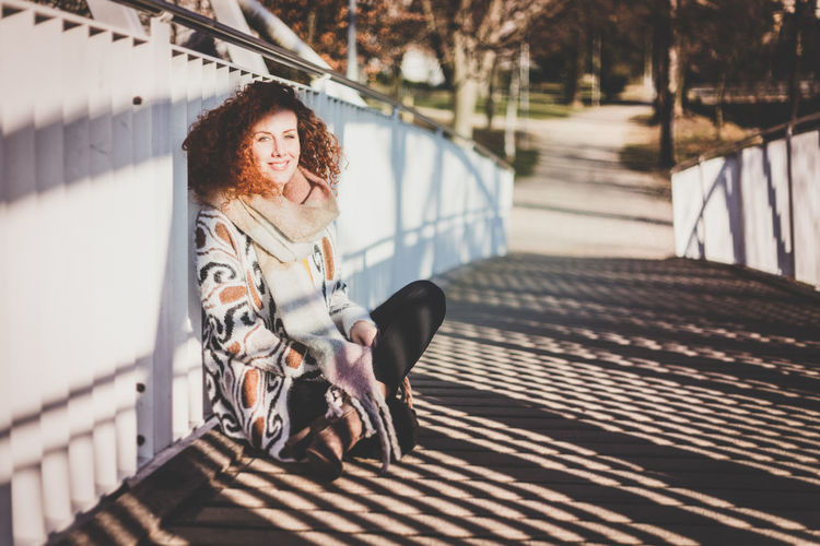 Portrait Of Woman Sitting On Footbridge