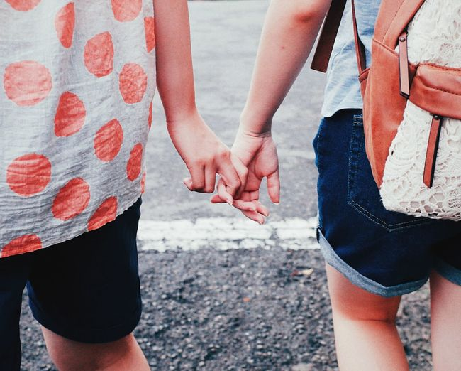 Midsection Of Girls Holding Hands On Street