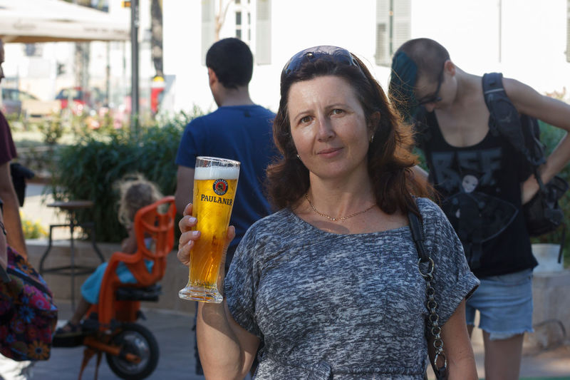 Tel Aviv, Israel, September 16, 2016: The beer festival visitor poses with a glass of beer in Tel Aviv, Israel Alcohol Annual Attractive Beer Celebration Clothes Costume Culture Dress Drink Event Festival Festive Folk Fun Glass Guest Happy Holiday Israel Mug Oktoberfest Smile Tel Aviv Traditional
