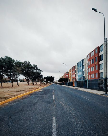 Empty road along trees and buildings