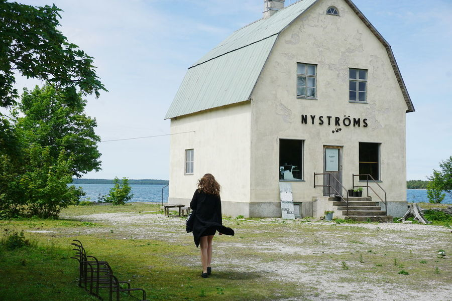 Young woman walking to the sea at Burgsvik, Sweden Adult Architecture Building Exterior Built Structure Burgsvik Day Full Length Gotland Gotland, Sweden Leisure Activity Lifestyles One Person Outdoors People Real People Rear View Sky Tree Women Sommergefühle