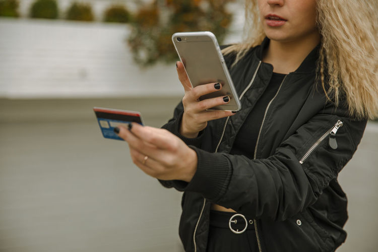 Midsection of woman using mobile phone in winter