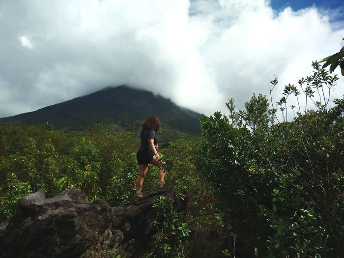 Full length of woman walking on rock in forest against sky