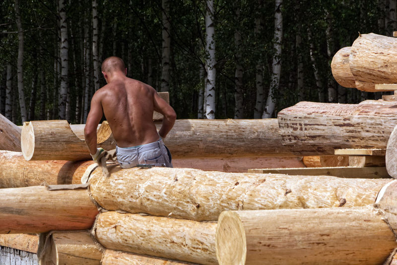 Full length of shirtless man standing on log in forest