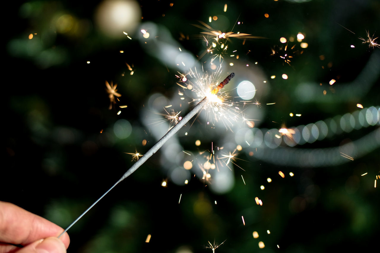 real people, hand, human hand, one person, illuminated, holding, sparkler, event, celebration, focus on foreground, selective focus, human body part, blurred motion, nature, sparks, glowing, motion, lens flare, close-up, outdoors, firework, firework - man made object, finger