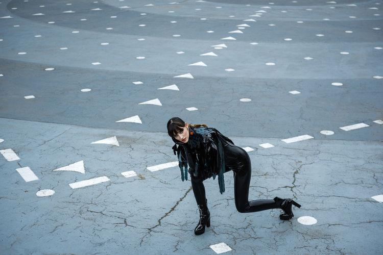 Portrait of female fashion model posing on footpath