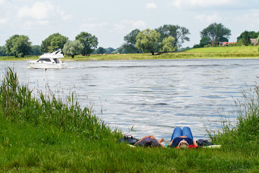 Beauty In Nature Boat Chilling Cloud - Sky Day Elbe River Field Grass Grassy Green Color Growth Idyllic Landscape Leisure Activity Lifestyles Lying Down Mode Of Transport Nature Outdoors River Scenics Tranquil Scene Tranquility Tree Water