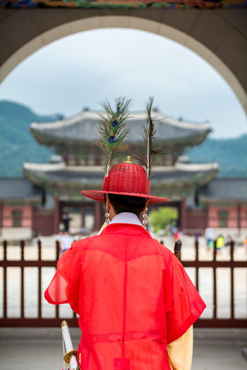 Rear view of man in traditional clothing and peacock feather at gwanghwamun