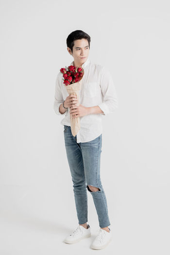 Full length portrait of a young handsome man carrying a flower bouquet and ready to meet his date One Person Studio Shot Front View White Background Standing Young Adult Full Length Indoors  Casual Clothing Looking At Camera Portrait Lifestyles Cut Out Copy Space Real People Adult Jeans Hairstyle Valentine's Day  Love Fashion Dating Rose - Flower Standing Guy