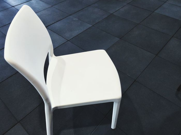 High angle view of empty white chair on tiled floor
