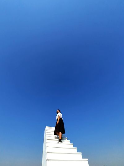 Low angle view of woman standing on steps against clear blue sky