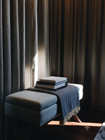 Books on seat by curtains at home