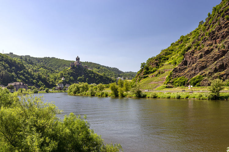 Scenic view of river by tree mountains against sky