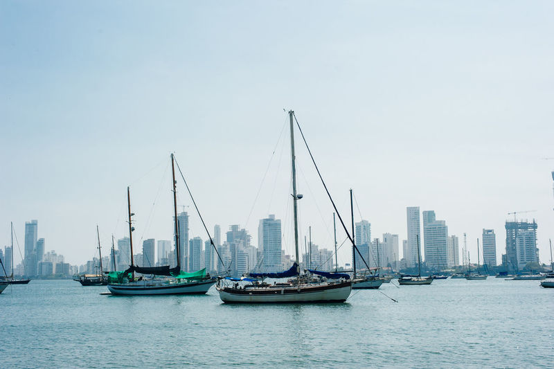 Sailboats in sea by buildings against clear sky