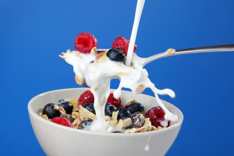 Close-up of fresh fruits in bowl against blue background