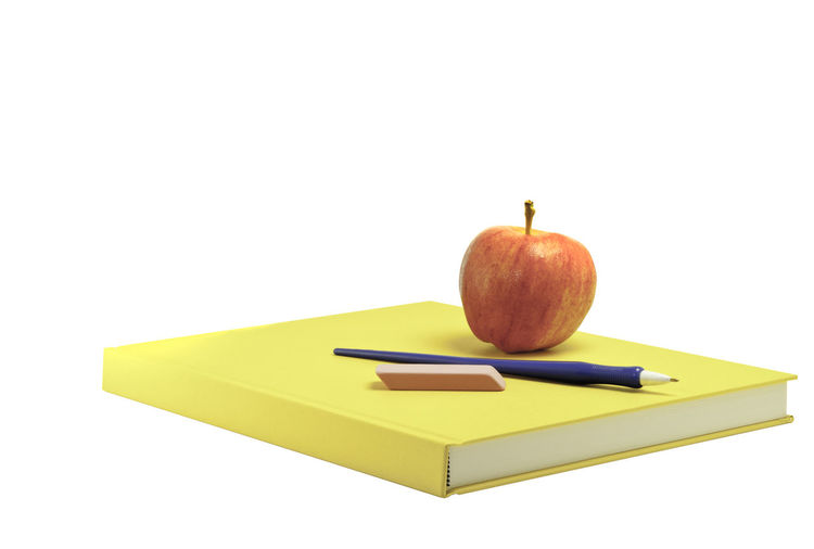 Close-Up Of Apple On Book Over White Background