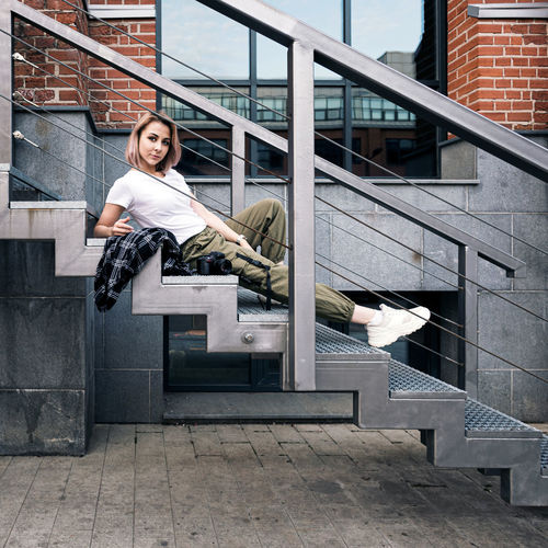 Hip hop style girl with a dslr camera  laying on metal stairs in an urban environment