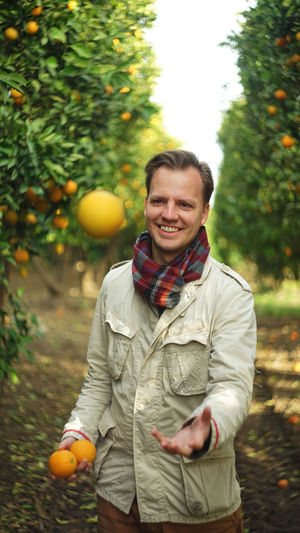 Smiling Food And Drink Portrait Happiness Fruit Food Orange Color Emotion Front View Real People Plant Day Lifestyles Tree Healthy Eating Young Men Orange Outdoors Orange - Fruit Orange Trees Juggling Village Garden Green