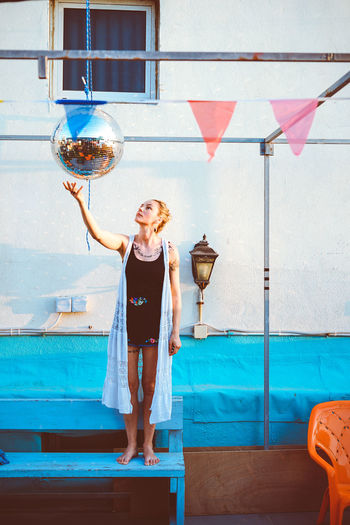 Woman reaching for disco ball hanging against wall