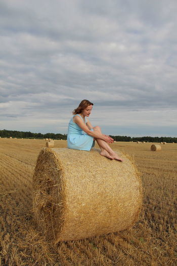 Full length of woman sitting on hay bales on agricultural land against cloudy sky