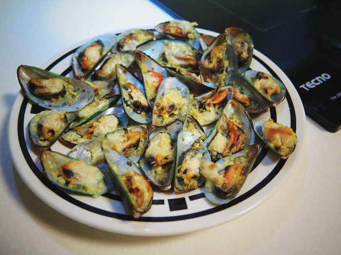 High Angle View Of Fresh Mussels Served In Plate On Table