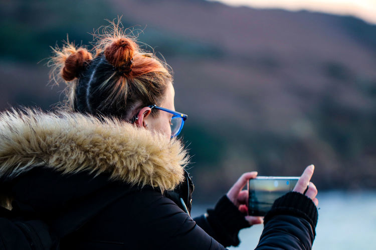 Side view of woman photographing through smart phone