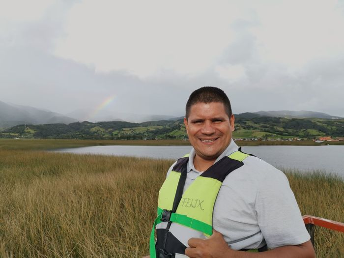 Portrait of smiling man standing on field by lake against sky