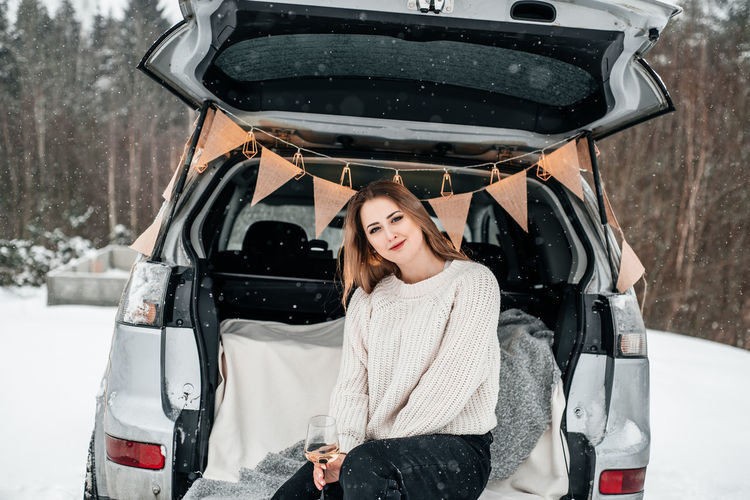 Portrait of smiling woman in snow by car trunk