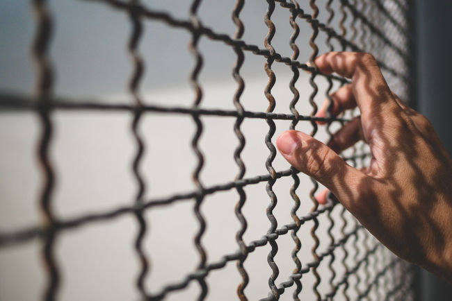 hand of prisoner holding metal fence with pattern shadow, criminal locked in jail waiting for freedom Hope Light Locked Stress Criminal Day Depress Despair Fence Human Hand Prison Release Sad Shadow Trapped