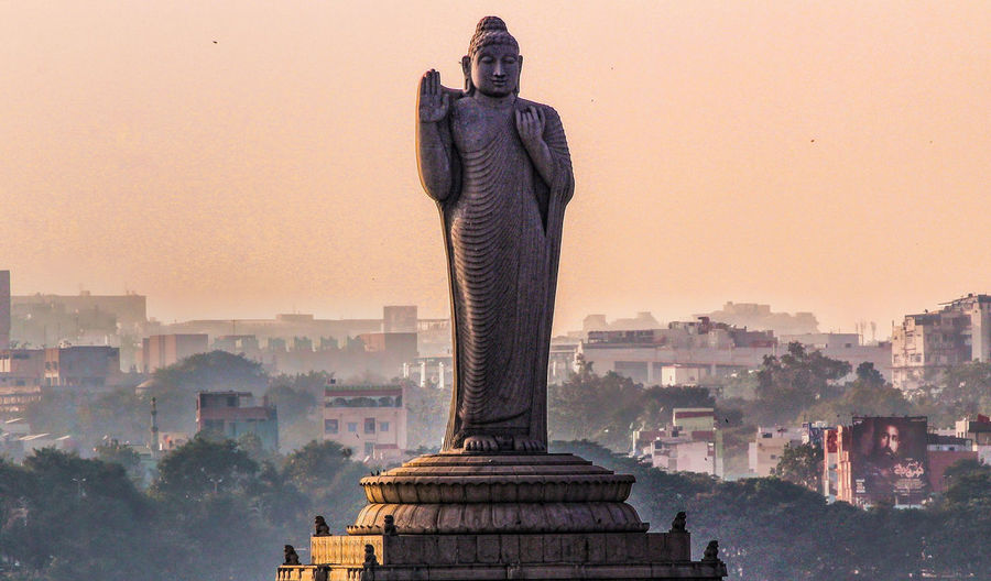 Buddha statue in city against clear sky during sunset