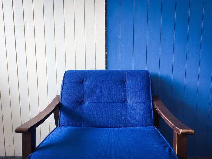 Empty Blue Armchair Against Wall