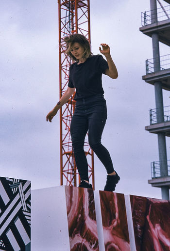 Full length portrait of young woman standing against ladder