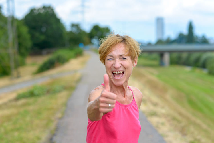 Mature woman gesturing thumbs up while exercising on road in park