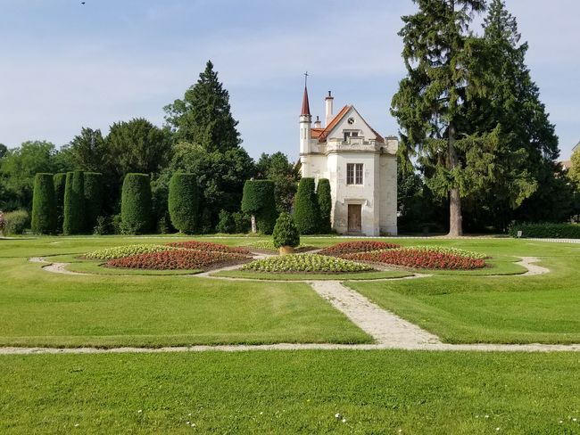 Formal garden at Lednice Castle. Czech It Out Europe Formal Garden UNESCO World Heritage Site Landmark Trees Flowers Flowerbed Path Walkway Design Sky Blue Sky Nature Architecture Hedge Topiary Garden Garden Photography Place Of Worship Yard Lush Foliage Tranquil Scene Lawn Green
