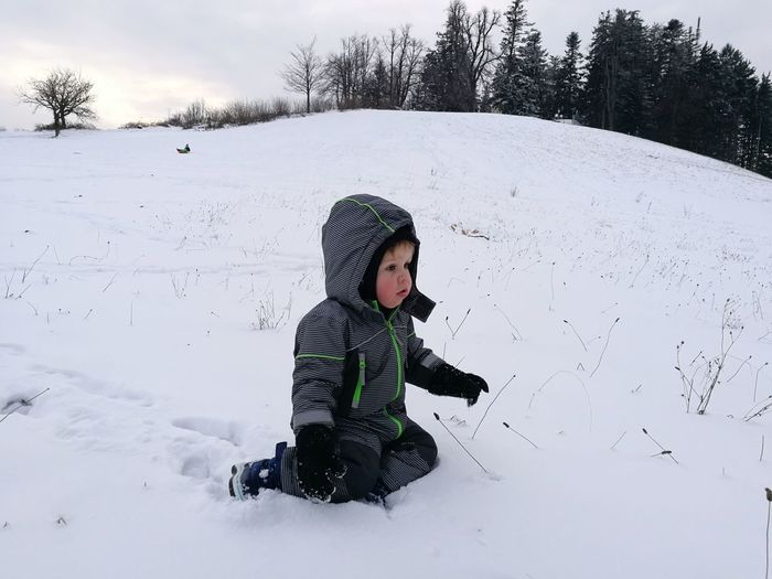 Boy Playing On Snow Field