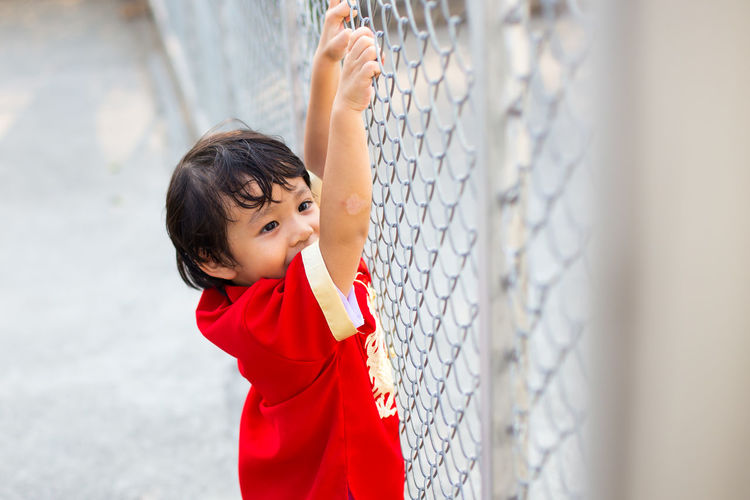 High angle view of playful boy holding chainlink fence