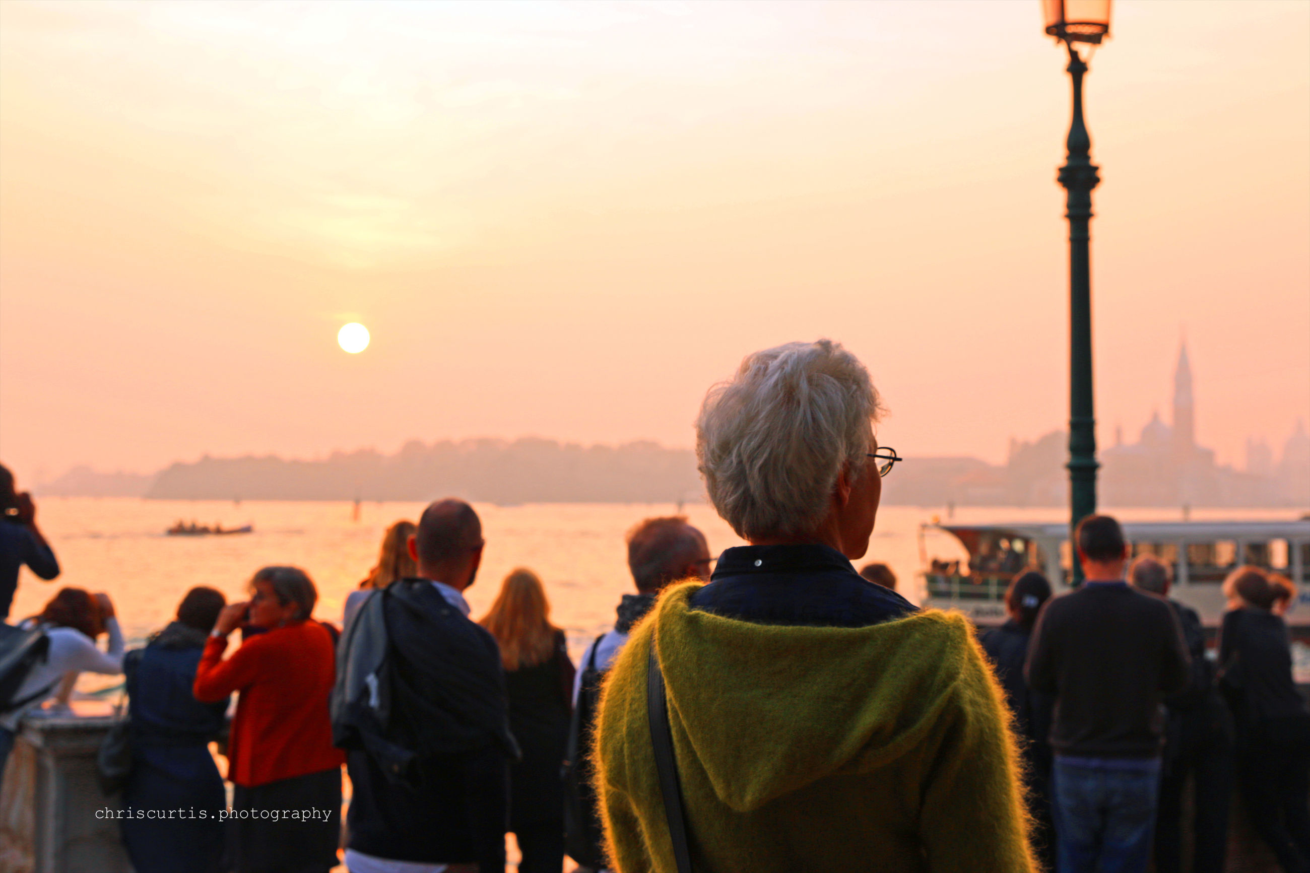sunset, real people, orange color, large group of people, rear view, leisure activity, men, sky, outdoors, lifestyles, enjoyment, nature, women, togetherness, travel destinations, city, beauty in nature, water, day, adult, people