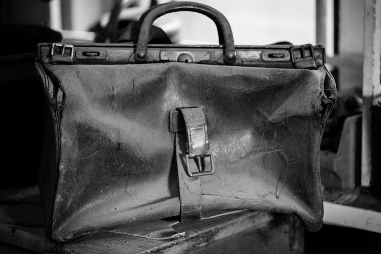 Close-up of abandoned weathered leather bag