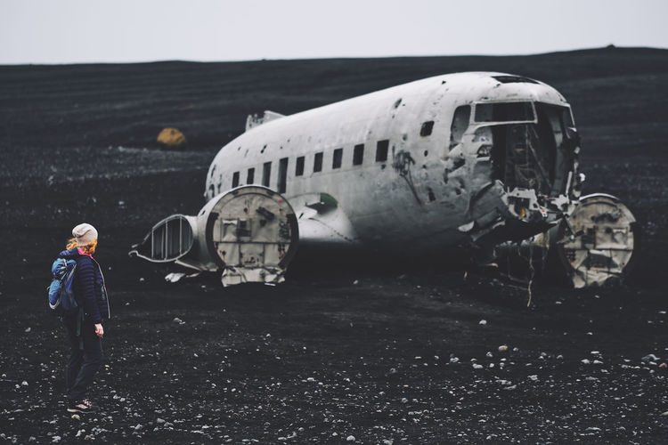Woman Looking At Abandoned Airplane Against Sky