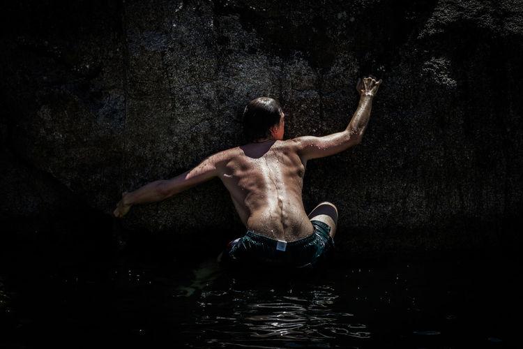 Rear View Of Shirtless Man Climbing On Concrete Retaining Wall