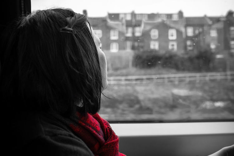 Close-Up Of Woman Looking Through Train Window
