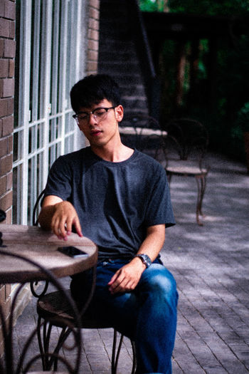 Boy Sitting Real People One Person One Animal Casual Clothing Adult Mammal Domestic Domestic Animals Glasses Men Lifestyles Front View Pets Leisure Activity Three Quarter Length Day Outdoors Contemplation